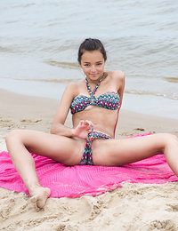 Adorable dark haired cutie with perfect skin is having fun on the beach showing her unique feminine curves in sexy lingerie.