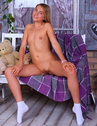 This perfect blonde babe wears white socks and spreads her legs to reveal her shaved pussy for your entertainment.